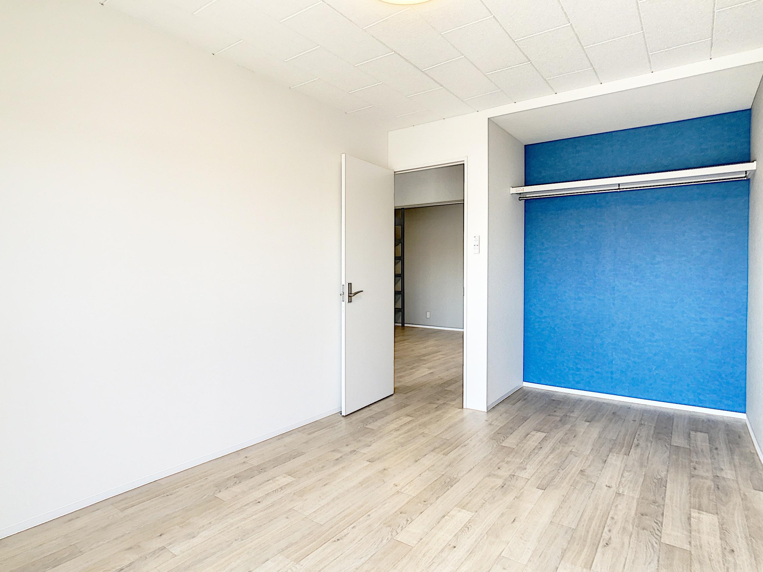 寝室のオープンクローゼットはブルーのクロスがアクセント