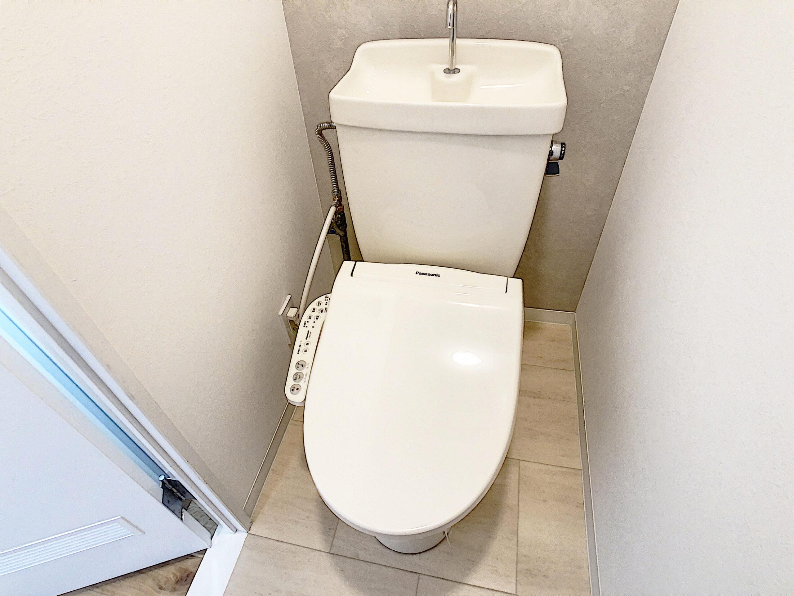 タイル風の床と塗り壁調クロスでシンプルだけどお洒落なトイレに