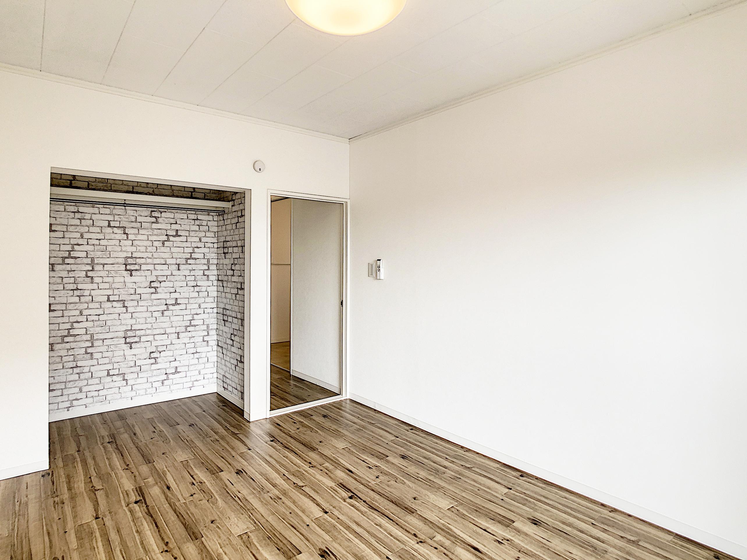 真っ白なお部屋にレンガ調のクロスのオープンクローゼットがアクセントに。