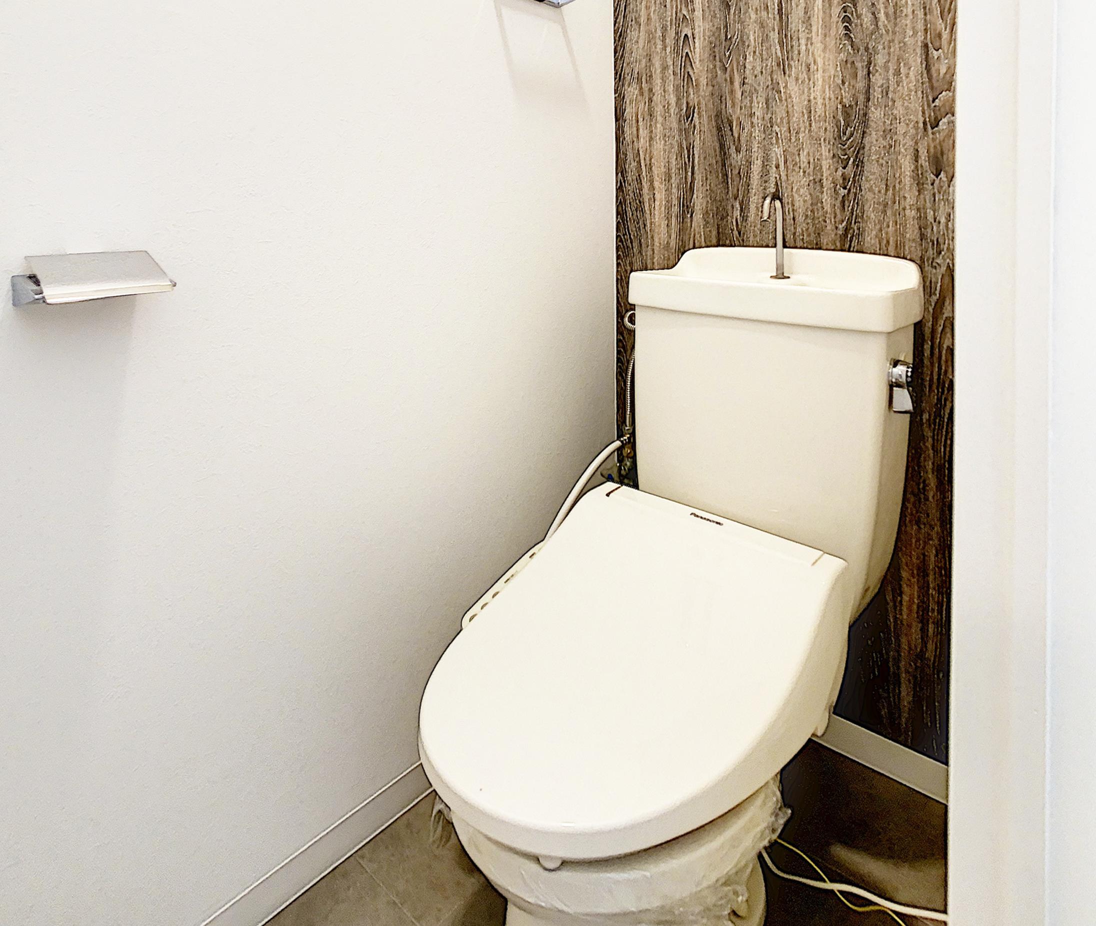 トイレは背面壁に木目のクロスを入れてナチュラルな空間を意識しました。